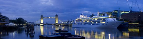 Tower Bridge and Cruise Liner. A cruise liner moored up to the HMS Belfast, near Tower Bridge at first light stock photography