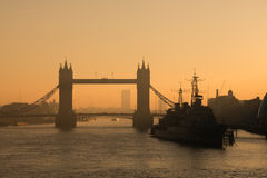 Tower Bridge at dawn. Partial silhouette of Tower Bridge and HMS Belfast at dawn in the City of London Stock Photos