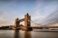 Tower Bridge at dusk. View over the River Thames to Tower Bridge. The Bridge arcs away from the viewpoint and its ancient stone is bathed in warm light from the royalty free stock photos