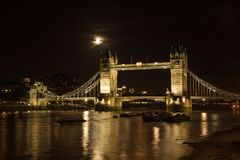 Tower bridge, full moon above, with river Thames illuminated in stock photo