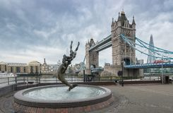 Tower bridge Girl and Dolphin statue against on a cloudy day Stock Images