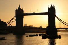 Tower Bridge in London at dawn. A dawn, sunrise silhouette of Tower Bridge in London, crossing over the River Thames, on a warm, clear spring morning stock image