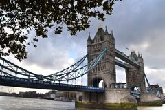 Tower Bridge London lateral view. And leaves of a tree in front Royalty Free Stock Images
