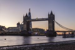 Tower Bridge in London at night or sunset. Old Tower Bridge in London at night or sunset over the river Thames with yellow light behind Royalty Free Stock Photos