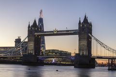 Tower Bridge in London at night or sunset. Old Tower Bridge in London at night or sunset over the river Thames with yellow light behind Stock Photos