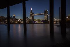 Tower Bridge in London at night or sunset. Old Tower Bridge in London at night or sunset over the river Thames with yellow light behind Stock Photo