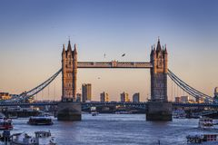 Tower Bridge in London at sunset. Old Tower Bridge in London at sunset over the river Thames with yellow light behind Royalty Free Stock Image