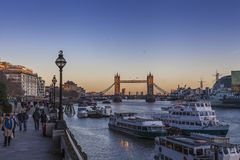 Tower Bridge in London at sunset. People passing by Tower Bridge in London at sunset over the river Thames with yellow light behind Royalty Free Stock Images