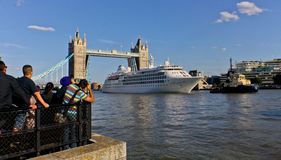 Tower Bridge. A luxury cruise liner passes through Tower Bridge in London. On the banks, tourists take photos while it passes by Royalty Free Stock Photo