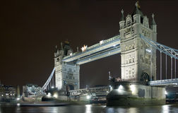 Tower Bridge at Night. With the blur of a boat approaching Stock Image
