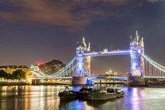 The Tower Bridge at night with boats on Thames river - London - Stock Photos