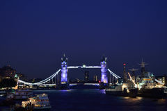 Tower Bridge at night. With several vessels in foreground Stock Photo
