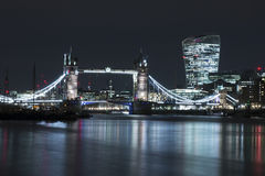 Tower Bridge at Night. Night view along the River Thames from Bermondsey towards the City of London. Tower Bridge illuminated in the foreground Stock Photos
