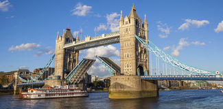 Tower Bridge Opened Up Over the River Thames. A panoramic view of Tower Bridge opening up over the River Thames to let a vessel pass underneath royalty free stock image