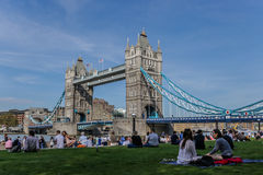 Tower Bridge and Potters Field, London. Tourists and locals enjoying sitting in Potters Field, next to Tower Bridge, on a sunny day Royalty Free Stock Image