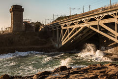 Tower and Bridge on Promontory near Shore Line. Tower on Promontory near Shore Line and Waves Crashing on Rocky Shore Stock Photography