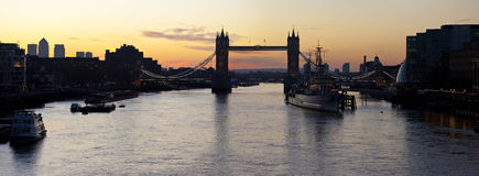 Tower Bridge and the River Thames Sunrise. A panoramic view of a London Sunrise taking in the sights of the river Thames, Tower Bridge, HMS Belfast and Docklands Royalty Free Stock Photo