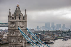 Tower Bridge and the skyscrapers of the financial district of Canary Wharf. Surrounded by low clouds on an overcast and foggy day Stock Image