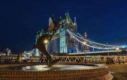 Tower Bridge and statue of a dolphin with girl playing at night Royalty Free Stock Photography