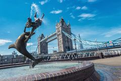 Tower Bridge and statue of a girl playing with dolphin in St Kat Stock Photo