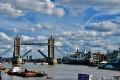 The river Thames and London Bridge. Tower Bridge stretching across the river thames in London under a silver lining clouds and blue sky royalty free stock photo