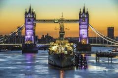 Tower Bridge at sunrise in London. Tower Bridge and HMS Belfast  at sunrise in London, England Stock Photo
