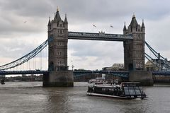 Tower Bridge and touristic boat in London. Tower Bridge and touristic boat going under the bridge,  in London, Great Britain Royalty Free Stock Image