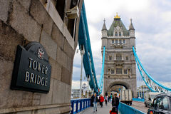 Tower Bridge. Tourists take photos on Tower Bridge in London. The Tower Bridge crosses the River Thames almost next to the Tower of London and has become an icon Stock Photo