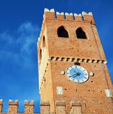 Tower, castle against blue sky, in Castelfranco Veneto, Italy, Europe. Clock tower, walls, castle against blue sky is placed in the centre square of Castelfranco royalty free stock photography