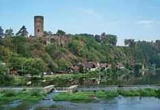 Castle ruins tower above a river stock image