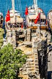 The tower of the castle of St. Peter in Bodrum. Among the tower is a round stone table, and in the background are visible yachts s royalty free stock photography