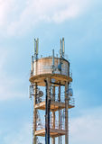 Tower with cellular communications. Old water tower with cellular communications Stock Images