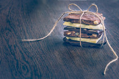 A tower of chocolate bars wrapped like a chocolate present . Various chocolate pieces over dark wood background. Royalty Free Stock Photo