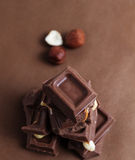 Tower of Chocolate. Hazelnuts and chocolate pieces on brown background.  Top view Royalty Free Stock Photography