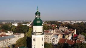 Tower of City Hall of Drohobych city with flag of Ukraine. Smooth pan around tower, cityscape. Tower of City Hall of Drohobych city with flag of Ukraine. Smooth stock video footage