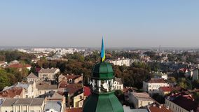 Tower of City Hall of Drohobych city with flag of Ukraine. Crane shot, cityscape.  stock video
