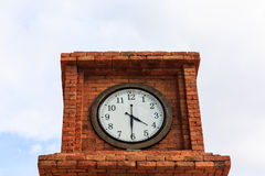 Tower clock between building. In public park with white sky Stock Images