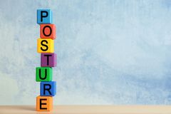 Tower of colorful cubes with word POSTURE. On wooden table stock photography