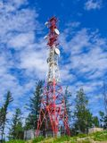 Tower of communication against the sky and green trees stock photography