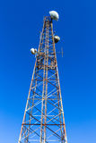 Tower Communications Radio TV Mobiles Signals. Steel tower against blue sky closeup vertical for radio tv mobiles signal communications Royalty Free Stock Photos