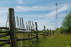 Tower connection. I think an interesting combination of old wooden fence and modern communications tower - two generations Royalty Free Stock Photo