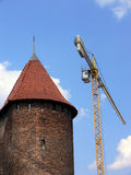 Tower With Crane. A brick tower shot against a blue cloudy sky with a crane beside it Royalty Free Stock Image