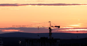 Tower crane against the backdrop of the setting sun. Backlight. Ekaterinburg, Russia Stock Photo