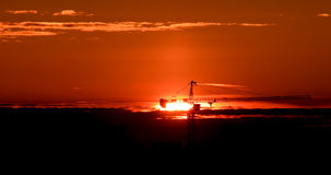 Tower crane against the backdrop of the setting sun. Backlight. Ekaterinburg, Russia Stock Image