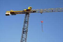 Tower crane against blue sky. Partial view of a yellow tower crane against blue sky Stock Photos