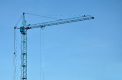 Tower crane against a blue sky. Abstract Industrial background with construction tower cranes over clear blue sky. Construction site. Building under construction Stock Photo