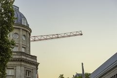 A tower crane behind a tall building at dusk. A tower crane behind a tall building at dusk royalty free stock photos