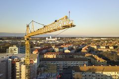 Tower crane on bright blue sky copy space background, city landscape stretching to horizon. Drone aerial photography.  stock image