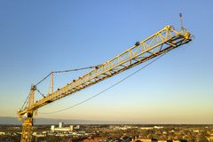 Tower crane on bright blue sky copy space background, city landscape stretching to horizon. Drone aerial photography.  stock photos