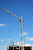 Tower Crane and building construction site  with contractor on the top. Industrial building. Stock Photo